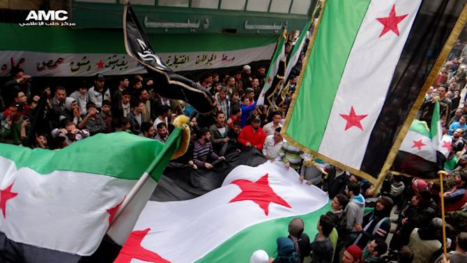 """In this citizen journalism image provided by Aleppo Media Center AMC which has been authenticated based on its contents and other AP reporting, anti-Syrian regime protesters, wave the Syrian revolutionary flags during a protest to mark the second anniversary of the their uprising, in Aleppo, Syria, Friday March 15, 2013. The chief of Syria's main, western-backed rebel group marked the second anniversary of the start of the uprising against President Bashar Assad on Friday by pledging to fight until the """"criminal"""" regime is gone. (AP Photo/Aleppo Media Center, AMC)"""
