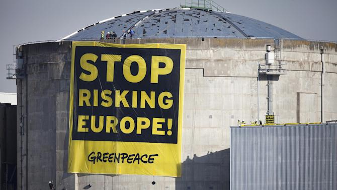 """In this photo provided by environmental group Greenpeace, activisits hang a banner reading """"Stop Risking Europe"""" at the Fessenheim nuclear power plant, eastern France, Tuesday, March 18, 2014. More than 60 Greenpeace activists have occupied a nuclear plant in eastern France to protest the nation's reliance on atomic power. In a statement Greenpeace France said the activists had come from 14 countries across Europe """"to denounce the risk to Europe from France's nuclear power,"""" and to promote a transition to other energy sources. (AP Photo/Daniel Mueller, Greenpeace) NO ARCHIVE"""