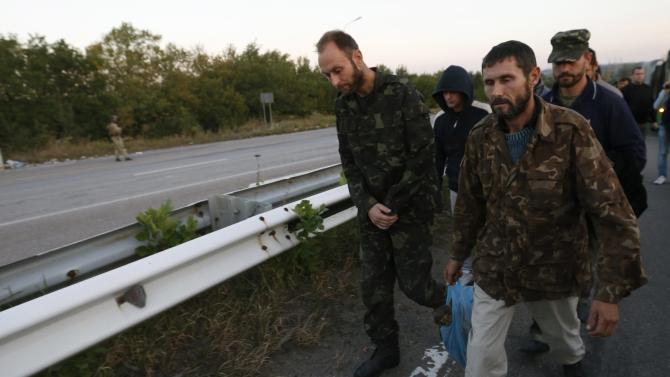 Members of the Ukrainian government forces, who are prisoners-of-war (POWs), walk along a road during a prisoner exchange near Donetsk