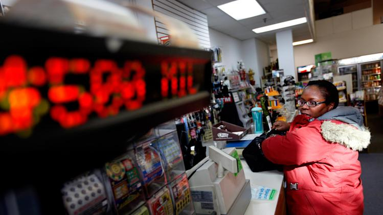 "Pat Powell, 30, of Atlanta, buys a Powerball lottery ticket at a convenience store, Wednesday, Nov. 28, 2012, in Atlanta. ""I think my odds are zero to zero,"" says Powell ""I don't think I'm going to win but I'll just join the hype. If I did win, I'd open up my own business, an internet café in the West Indies and have a learning center here in Georgia. I'll invest and  try to be as smart with it as I can with it. I will say for the past 3 days, for whatever reason, I've been thinking about winning this money and what I'd do with it. There's no ritual but it's just been on my mind so it's like, let me just join the hype and just do it."" (AP Photo/David Goldman)"
