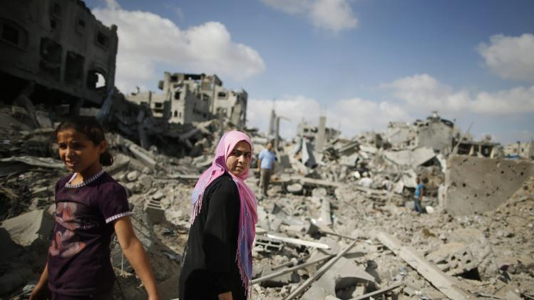Palestinians inspect destroyed houses in the Shejaia neighbourhood, which witnesses said was heavily hit by Israeli shelling and air strikes during an Israeli offensive, in Gaza City