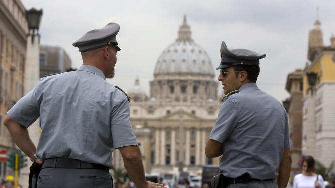 FILE - In this Tuesday, Sept. 21, 2010 file photo Italian financial Police officers talk, in front of St. Peter's square at the Vatican.    The Vatican is being besieged by near-daily leaks of confidential documents and tabloid-style reports about alleged money laundering at the Vatican bank, and in news reports Saturday Feb. 11, 2012, some conspiracy theorists highlight the upcoming crowning of 22 new cardinals, who will be partly responsible for electing the successor to the Pope himself. (AP Photo/Angelo Carconi, File)