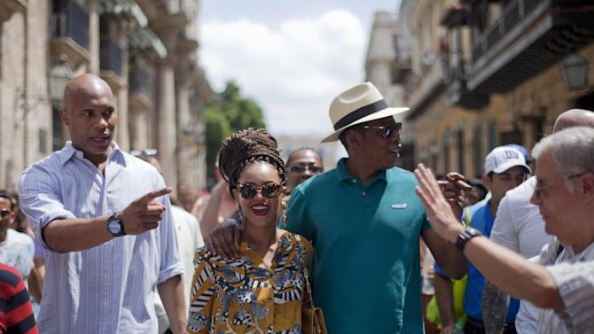 U.S. singer Beyonce and her husband, rapper Jay-Z, right, tours Old Havana as a body guard, left, and tour guide, right, accompany them in Cuba, Thursday, April 4, 2013. R&B's power couple is in Havana on their fifth wedding anniversary. (AP Photo/Ramon Espinosa)