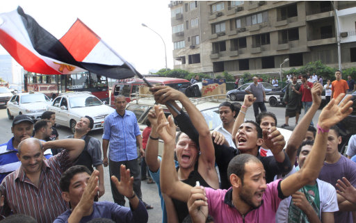 Egyptian activists wave their national flag near the Israeli embassy in Cairo, Egypt, Saturday, Sept. 10, 2011. President Barack Obama has assured Israeli Prime Minister Benjamin Netanyahu that the U.S. is taking steps