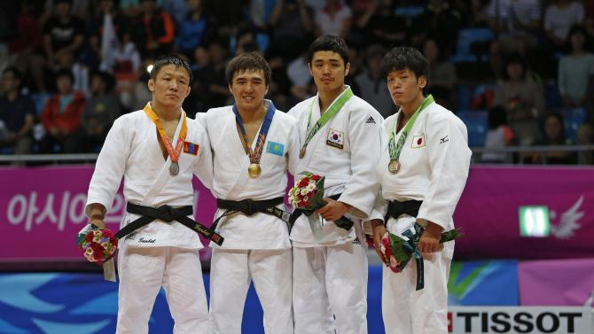 Gold medallist Smetov of Kazakhstan poses with silver medallist Ganbat of Mongolia and bronze medallists Shishime of Japan and Kim of South Korea during an awarding ceremony for their men's -60kg judo match during the 17th Asian Games in Incheon