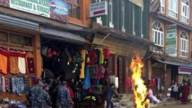 Nepalese policemen rush as a Tibetan monk burns after he set himself on fire in Katmandu, Nepal, Wednesday, Feb. 13, 2013. The Tibetan monk doused himself with gasoline and set himself on fire in Nepal's capital Wednesday in what is believed to be the latest self-immolation to protest Chinese rule in Tibet. Nearly 100 Tibetan monks, nuns and lay people have set themselves on fire in various countries, mostly in ethnic Tibetan areas inside China, since 2009.( AP Photo)