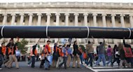 Demonstrators carry a giant mock pipeline while calling for the cancellation of the Keystone XL pipeline during a rally in front of the White House in Washington November 6, 2011. REUTERS/Joshua Roberts