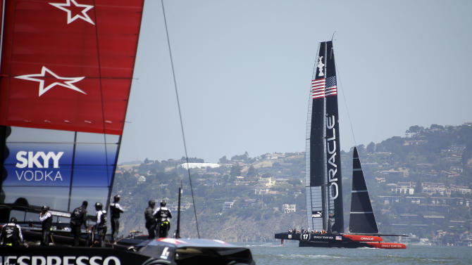 Crew members aboard Emirates Team New Zealand, left, watch as Oracle Team USA sails past during training for the America's Cup Friday, May 24, 2013 in San Francisco. (AP Photo/Eric Risberg)