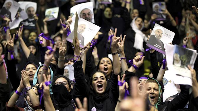 """FILE - In this Saturday, June 8, 2013 file photo, female supporters of the Iranian presidential candidate, Hasan Rouhani, chant slogans during a campaign rally in Tehran, Iran. Just before leaving for New York on Monday, Sept. 23, 2013, Rouhani urged Western leaders to heed his appeals for greater dialogue and take steps to ease sanctions as a way to """"reach joint interests,"""" a reference to the nuclear standoff, but also possibly other regional flash points where Iran carried influence such as Iraq and Syria. (AP Photo/Ebrahim Noroozi, File)"""