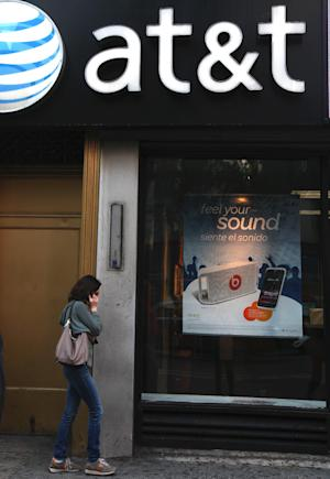FILE-In this May 6, 2012, file photo, a woman talks on her cell phone outside an AT&T store in New York. AT&T is seeing declining smartphone sales, leading to the best profitability ever in its wireless arm as it saves on phone subsidies. The largest telecommunications company in the U.S. says it activated 5.1 million smartphones in its latest quarter, down from 5.5 million in the same period a year ago. (AP Photo/CX Matiash,File)