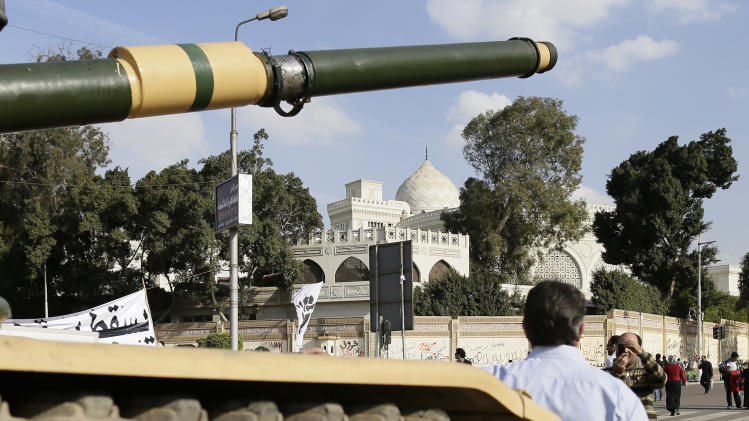An Egyptian protester takes a picture with his mobile of another in front of an  Egyptian army tank outside the presidential palace, background, in Cairo, Egypt, Saturday, Dec. 8, 2012. Egypt's military has warned of 'disastrous consequences' if the political crisis gripping the country is not resolved through dialogue. (AP Photo/Hassan Ammar)