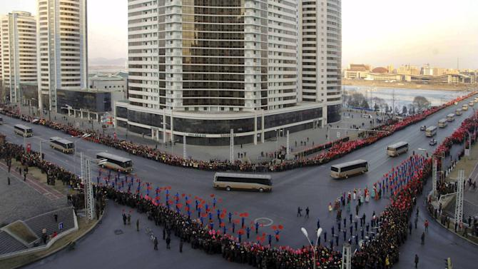 People wave flags as members of operation team of Kwangmyongsong-4 long range rocket arrive at Pyongyang