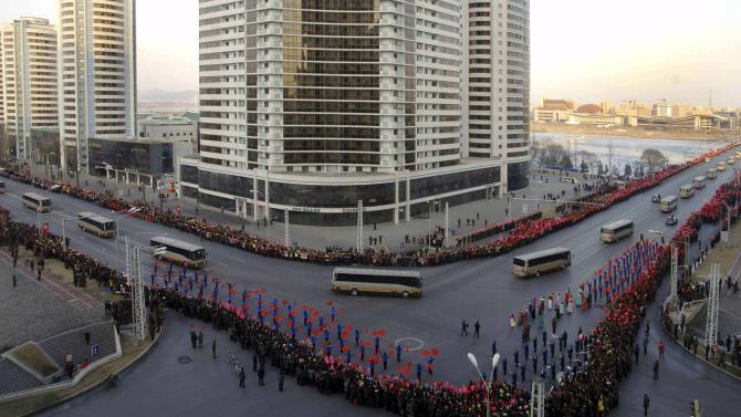People wave flags as members of operation team of Kwangmyongsong-4 long range rocket arrive at Pyongyang