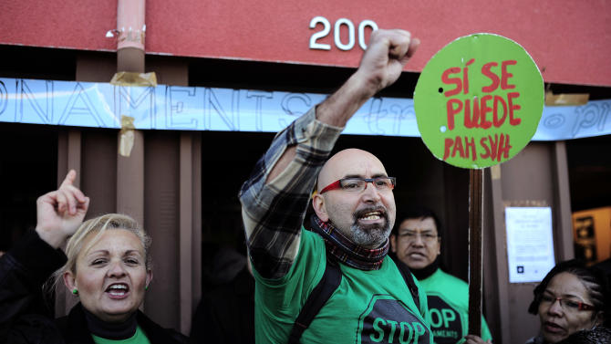 """Members of the Mortgage Victims' Platform (PAH) react after an eviction was stopped in Barcelona, Spain, Wednesday, Jan. 29, 2014. Spain's National Statistics Agency says the unemployment rate for the fourth quarter of 2013 edged up slightly, leaving it stuck at the sky-high level of 26 percent and that the number of unemployed stood at a rounded 5.9 million people. Government officials say Spain's sluggish economy is stabilized and on track for job growth but economists predict it will take years to bring the jobless rate down to a more tolerable level. The banner reads in Spanish: """"Yes, we can."""" (AP Photo/Manu Fernandez)"""