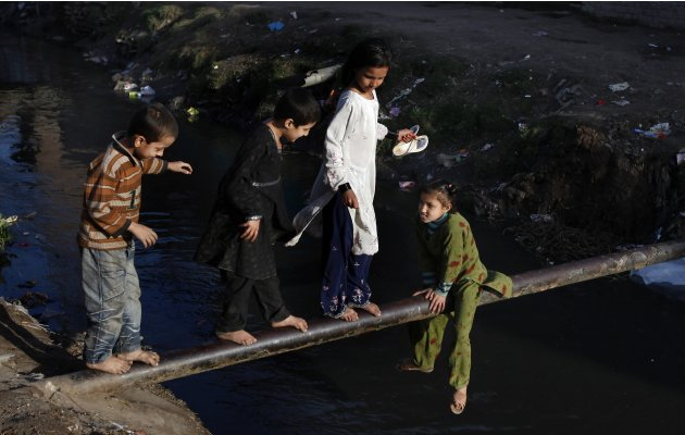 Children play on a water pipe in the main sewerage area in Lahore