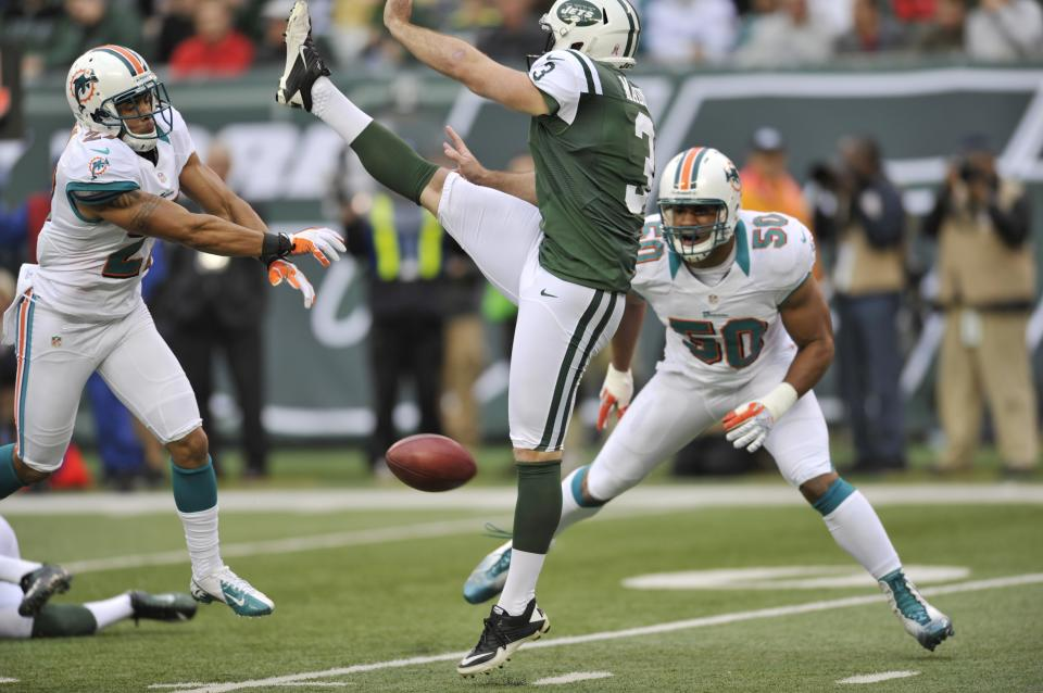New York Jets Robert Malone (3) has his punt blocked by Miami Dolphins' Jimmy Wilson, left, during the first half of an NFL football game as Olivier Vernon (50) returned the punt for a touchdown on the play Sunday, Oct. 28, 2012 in East Rutherford, N.J. (AP Photo/Bill Kostroun)