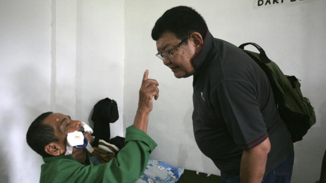 In this Sunday, Nov. 4, 2012 photo, 70-year-old Maskut reaches to touch the nose of Dr. Sanduk Ruit, right, to prove that he can see after his eye patches were removed following his cataract surgery the night before at a military hospital in Padang Sidempuan, North Sumatra, Indonesia. Indonesians flocked to the hospital for free cataract surgery performed by a team led by Nepalese master surgeon Dr. Sanduk Ruit who is renowned for his high-volume assembly-line approach. During the eight-day eye camps held in two towns in North Sumatra, more than 1,400 cataracts were removed. (AP Photo/Binsar Bakkara)