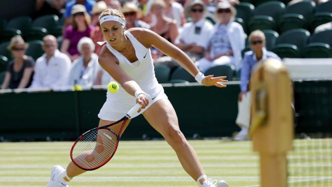 Sabine Lisicki of Germany hits a shot during her match against Timea Bacsinszky of Switzerland at the Wimbledon Tennis Championships in London