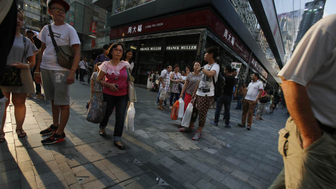 Mainland China tourists walk past the luxury boutiques of Tsim Shai Tsui district in Hong Kong, Wednesday, Oct. 1, 2014. Despite the expansion of the pro-democracy protests to the luxury shopping district of Tsim Shai Tsui favored by mainland tourists, most mainlanders were more interested inshopping than inany political activities. (AP Photo/Wally Santana)