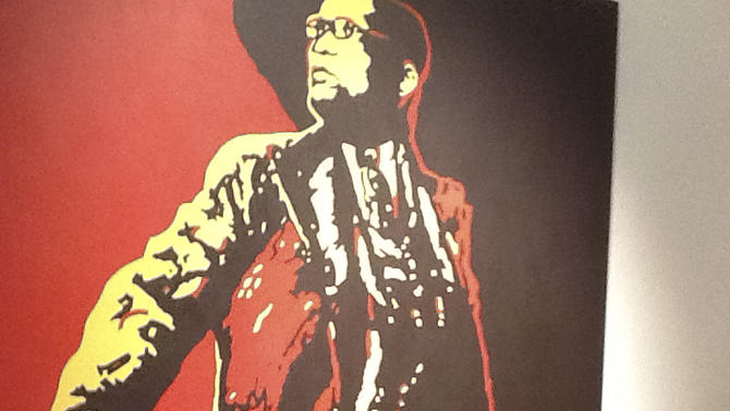 An unidentified man defaces a controversial portrait of South African President Jacob Zuma at the Goodman Gallery in Johannesburg, South Africa, Tuesday May 22, 2012. Footage shown on a national news station showed a man in a suit painting a red X over the president's genital area and then his face. Next a man in a hoodie rubbed black paint over the president's face and down the painting with his hands. (AP Photo/eNews)