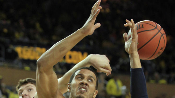 Arkansas forward Hunter Mickelson knocks the ball away from Michigan forward Jordan Morgan (52) during the second half of an NCAA college basketball game in Ann Arbor, Mich., Saturday, Dec. 8, 2012. (AP Photo/Carlos Osorio)