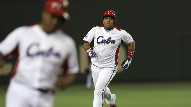 Cuba's rightfielder Yasmany Tomas, right, rounds bases after hitting a three-run homer off Taiwan's pitcher Yang Yao-hsun in the fourth inning of their World Baseball Classic second round game at Tokyo Dome in Tokyo, Saturday, March 9, 2013. At left rounding third base is teammate Alfredo Despaigne. (AP Photo/Toru Takahashi)