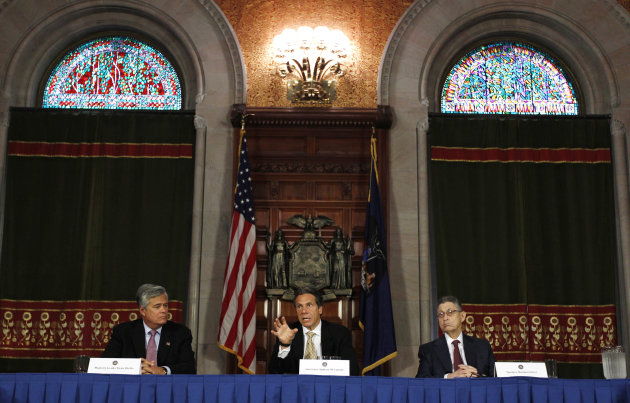 New York Gov. Andrew Cuomo, center, speaks during a news conference in the Red Room at the Capitol as Senate Majority Leader Dean Skelos, R-Rockville Center, left, and Assembly Speaker Sheldon Silver,