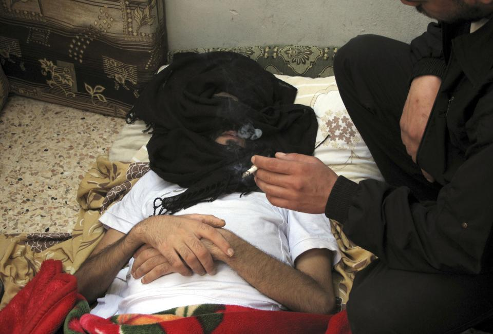 A Syrian man wounded by the government troops gets treated in a Damascus neighborhood, Syria, Tuesday, April 3, 2012. A Syrian government official said Tuesday that the troops have begun withdrawing from some cities and are returning to their bases. (AP Photo)