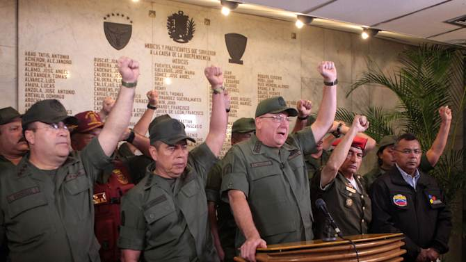 In this photo released by Miraflores Presidential Press Office, Venezuela's Defense Minister Admiral Diego Molero, at the podium, gestures alongside other military leaders during a live televised message to the nation after the vice president announced the death of President Hugo Chavez in Caracas, Venezuela, Tuesday, March 5, 2013.  Molero announced that the military will remain loyal to the constitution in the wake of Chavez's death. (AP Photo/Miraflores Presidential Press Office)