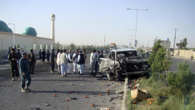 Afghan Policemen investigate at the site of a suicide car bomb attack in Helmand province southern Afghanistan, Monday, June 17, 2013. An Afghan police chief Mohammad Nabi Elham survived the attack on his convoy that wounded three officers early Monday, officials said. (AP Photo/Abdul Khaliq Kandahari)