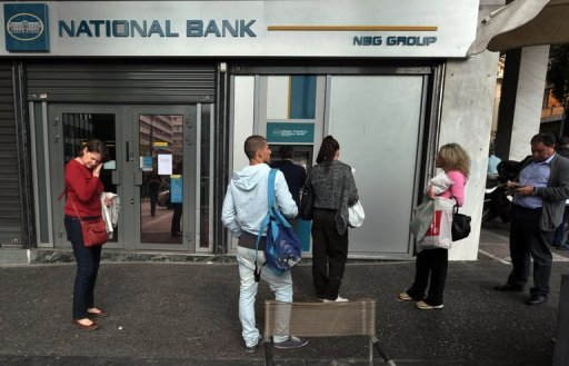 <p>People queue at a cash machine outside a bank in Athens. Shares in Greek banks plunged, dragging down the entire Greek stock market on Monday on new tensions over recapitalisation of Greek banks and delays to quarterly results.</p>