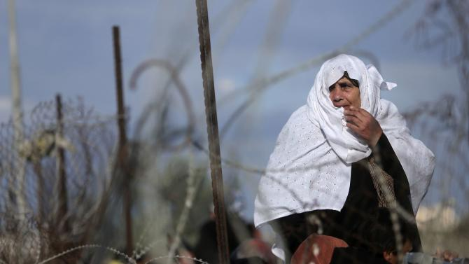 Palestinian woman, hoping to cross into Egypt, stands behind a fence as she waits at the Rafah crossing between Egypt and the southern Gaza Strip