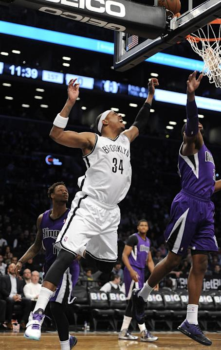Brooklyn Nets' Paul Pierce (34) reaches for a loose ball with Sacramento Kings' Jason Thompson (34) in the first half of an NBA basketball game on Sunday, March 9, 2014, at Barclays Center in