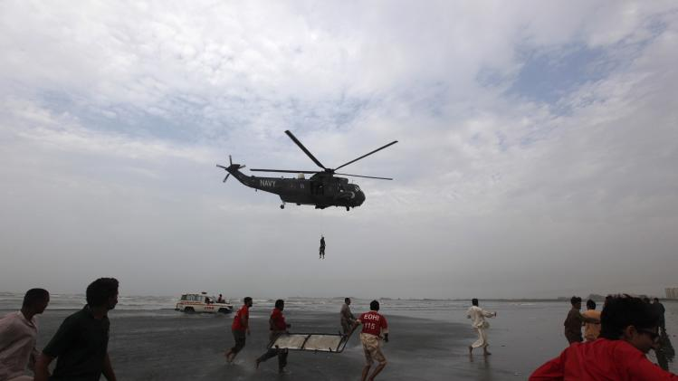 Rescue workers in red shirts carry a stretcher as they run to receive the body of a victim who had drowned on Wednesday, from a Pakistan Navy helicopter, at Karachi's Clifton beach