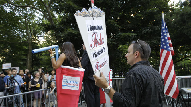"""Danny Panzella listens to speakers, including Dan Halloran who is running for Congress, during a """"Million Gulp"""" demonstration against Mayor Michael Bloomberg's proposal to prohibit licensed food establishments from using containers larger than 16 ounces to serve high-calorie drinks like colas at City Hall in New York, Monday, July 9, 2012. in New York, Monday, July 9, 2012. (AP Photo/Kathy Willens)"""