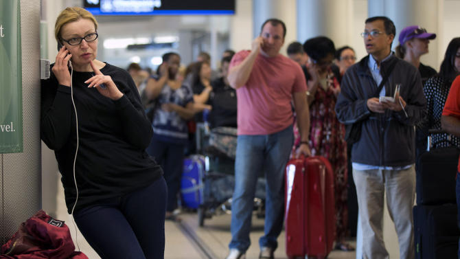 An unidentified woman tries to call the American Airlines reservation center, Tuesday, April 16, 2013, as she stands in line at the Miami International Airport in Miami. A computer system used to run many daily operations at American Airlines failed Tuesday, forcing the nation's third-largest carrier to ground all flights across the United States for several hours and stranding thousands of frustrated passengers at airports and on planes. (AP Photo/J Pat Carter)