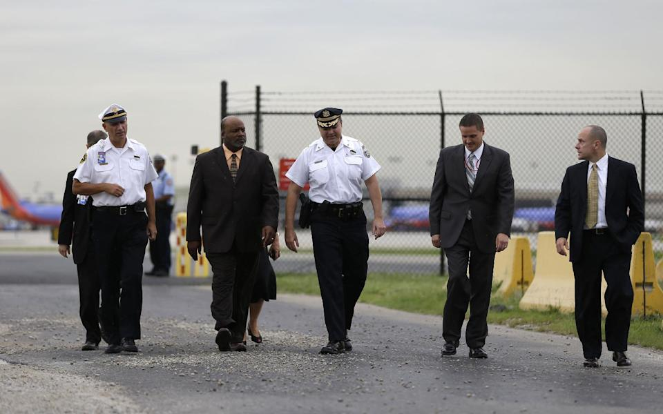 Philadelphia police Chief Inspector Joseph Sullivan, center in white, walks to a news conference with airport and law enforcement officials near the Philadelphia International Airport Thursday, Sept. 6, 2012, in Philadelphia. A security scare that prompted authorities to recall an airborne U.S. flight was the result of an apparent hoax, police said Thursday. (AP Photo/Matt Rourke)