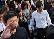 Pastor Kong Hee (R in white shirt) holds his wife Ho Yeow Sun&#39;s hand as they leave court in Singapore on June 27, 2012. The Singapore-based Christian church rocked by a massive financial scandal has stood by its founder and four aides who could face life imprisonment for allegedly misusing the congregation&#39;s funds