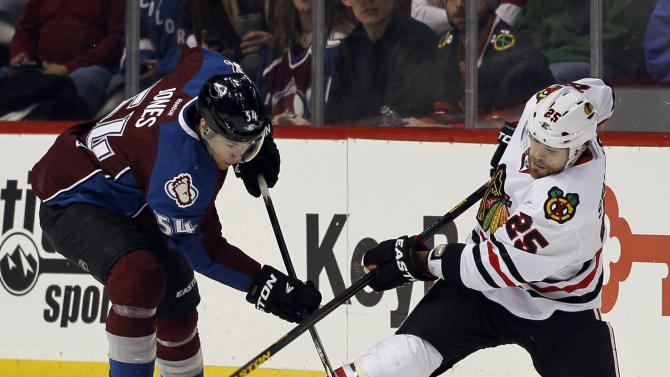 Chicago Blackhawks right wing Viktor Stalberg, right, of Sweden, clears the puck from along the boards as Colorado Avalanche right wing David Jones covers in the first period of an NHL hockey game in Denver, Friday, March 8, 2013. (AP Photo/David Zalubowski)