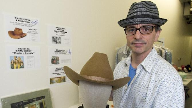"In this Friday, Nov. 30, 2012 photo, James Comisar shows a Stetson hat worn by actor Larry Hagman portraying oil tycoon J. R. Ewing in the ""Dallas"" television show. The item is part of his television memorabilia collection in a temperature- and humidity-controlled warehouse in Los Angeles. (AP Photo/Damian Dovarganes)"