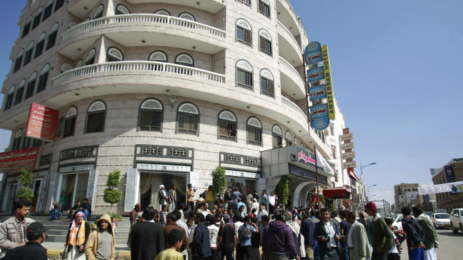 Yemenis gather after a Russian military expert was shot dead in front of Hotel Amsterdam on a street in Sanaa, Yemen, Tuesday, Nov. 26, 2013. Unknown gunmen in Yemen killed a foreign military expert and wounded his colleague in a drive-by shooting Tuesday in the capital, a Yemeni security official said. (AP Photo/Hani Mohammed)