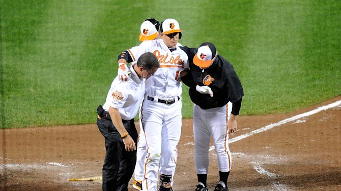 Manny Machado of the Baltimore Orioles is helped off the field after injuring his leg in the third inning against the New York Yankees at Camden Yards on August 11, 2014 in Baltimore