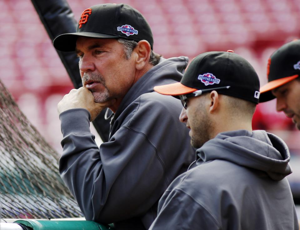 San Francisco Giants manager Bruce Bochy, left, watches batting practice with Marco Scutaro prior to Game 4 of the National League division baseball series against the Cincinnati Reds, Wednesday, Oct. 10, 2012, in Cincinnati. (AP Photo/David Kohl)