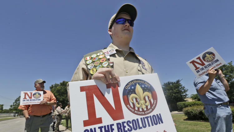 Matthew Ray, 15, of North Richland Hills, Texas, holds signs near where the Boy Scouts of America are holding their annual meeting Wednesday, May 22, 2013, in Grapevine, Texas. Delegates to the meeting are expected to address a proposal to allow gay scouts into the organization. (AP Photo/LM Otero)
