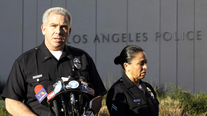 LAPD spokesman Lt. Andy Neiman, left, with officer Norma Eisenman, talks to reporters during a news briefing at LAPD headquarters regarding Christopher Dorner, who is suspected of a deadly revenge plot against the Los Angeles Police Department on Wednesday, Feb. 13,2013. Neiman said  the department has returned to normal patrol operations and said approximately a dozen of the more than 50 protective details remain in place and will stay that way until the remains of Dorner are positively identified.(AP Photo/Richard Vogel)