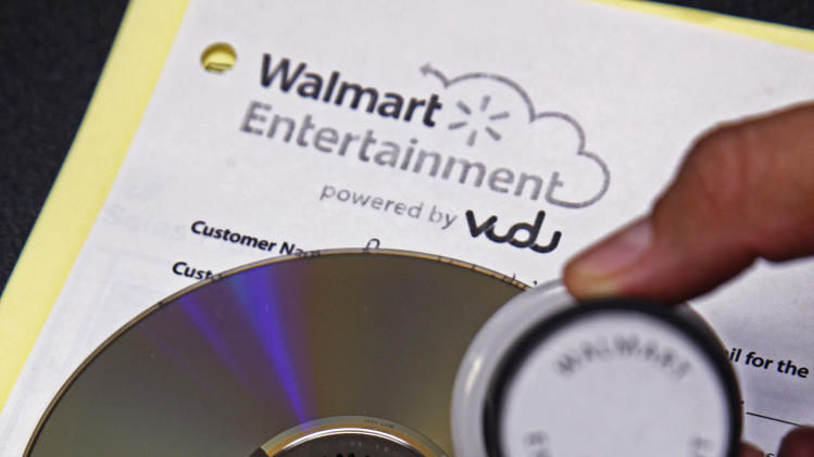 "A ""Walmart Entertainment"" stamp in indelible ink has been placed on a disc, preventing any further conversion, but allowing it to still be played, at a Wal-Mart store in Rosemead, Calif., Wednesday, April 11, 2012. Wal-Mart is set to unveil its ""disc-to-digital"" service for converting old DVDs into an online library that is available over the Internet. The fee it will charge per disc is meant to cover the cost of hosting and delivering reams of movie files to various devices. The world's largest retailer also aims to keep drawing customers to its big-box stores as their movie-watching habits change. (AP Photo/Reed Saxon)"