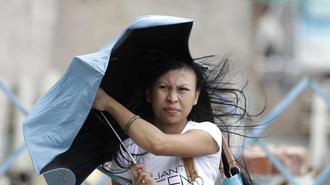 A woman holds her umbrella while walking against strong winds as tropical storm Fung-wong hits Taiwan, in Taipei