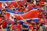 North Korean fans cheer their team before the start of the women&#39;s 1st round football match against Germany at the 2008 Beijing Olympic Games