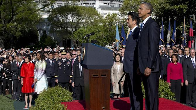 President Barack Obama hosts a state arrival ceremony for Japanese Prime Minister Shinzo Abe, Tuesday, April 28, 2015, on the South Lawn of the White House in Washington. Abe's wife Akie Abe, left in red, and first lady Michelle Obama are at left. (AP Photo/Jacquelyn Martin)