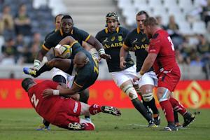 South Africa's wing Cornal Hendricks (C) is tackled…
